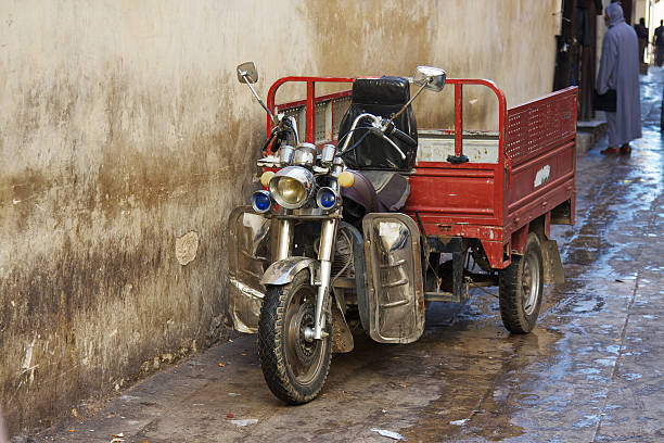 Three wheel motorcycle in Fez Medina. Morocco. An old Three wheel motorcycle with red cassone parked in Fez Medina. Morocco. three wheel motorcycle stock pictures, royalty-free photos & images