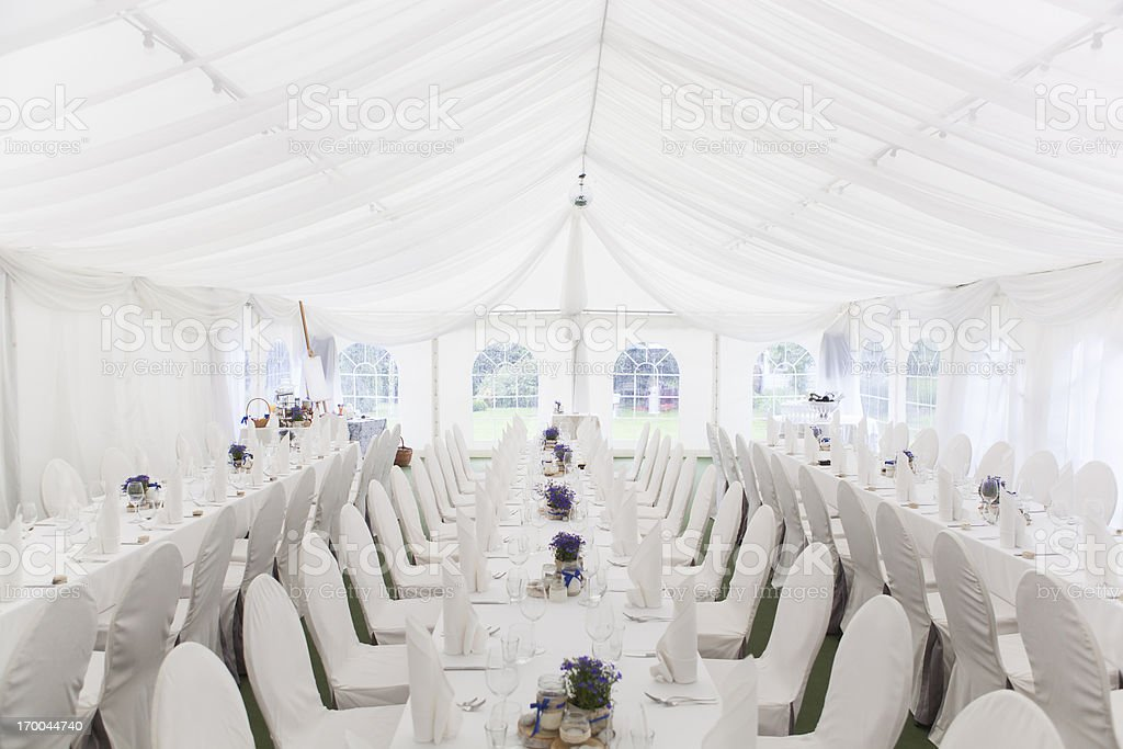 Three white banquet tables with white settings stock photo