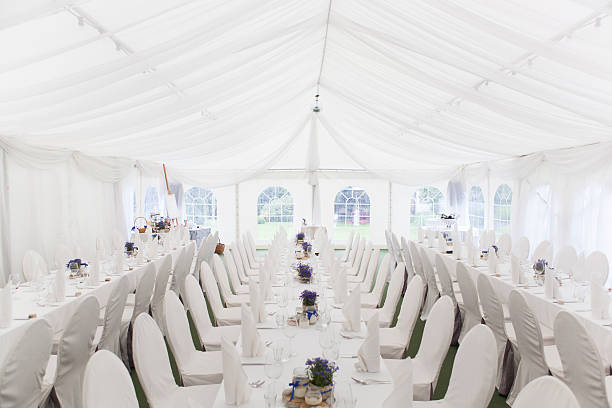 Three white banquet tables with white settings Banquet Table Setting for a Celebration Event. entertainment tent stock pictures, royalty-free photos & images