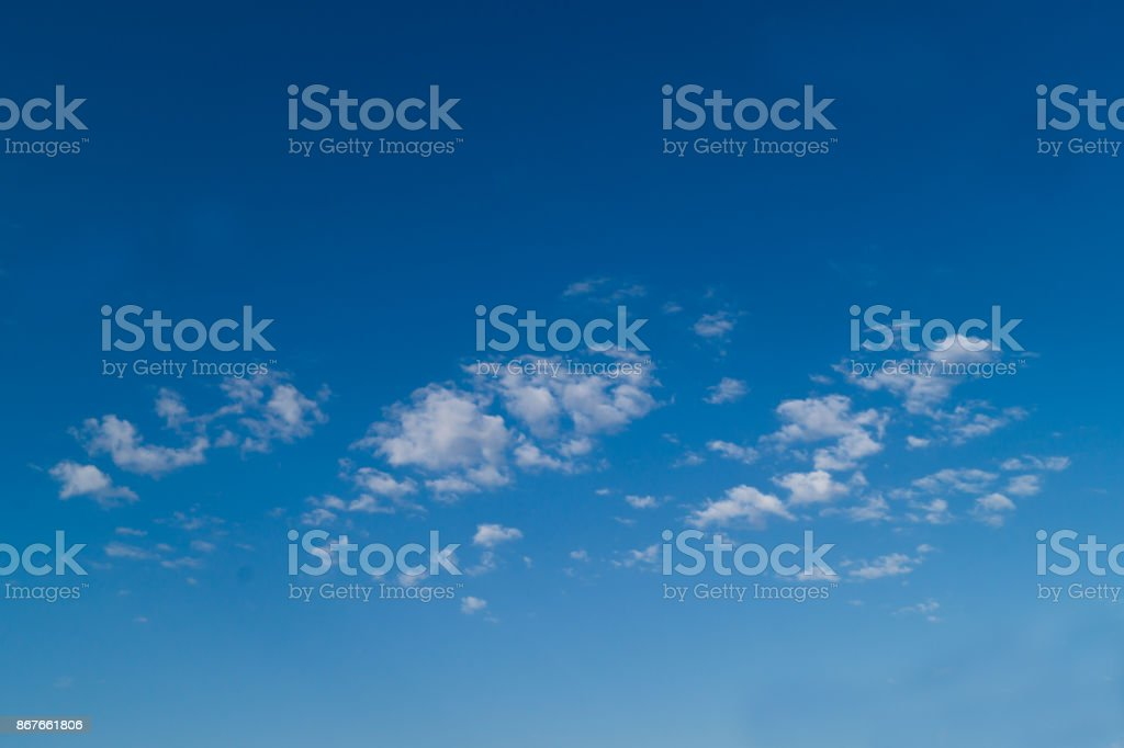 Three white fkuffy small clouds on the light-blue sky stock photo