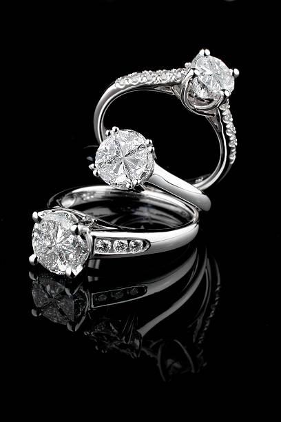 drei weiße gold diamond ringe auf schwarzem hintergrund - diamantschmuck stock-fotos und bilder