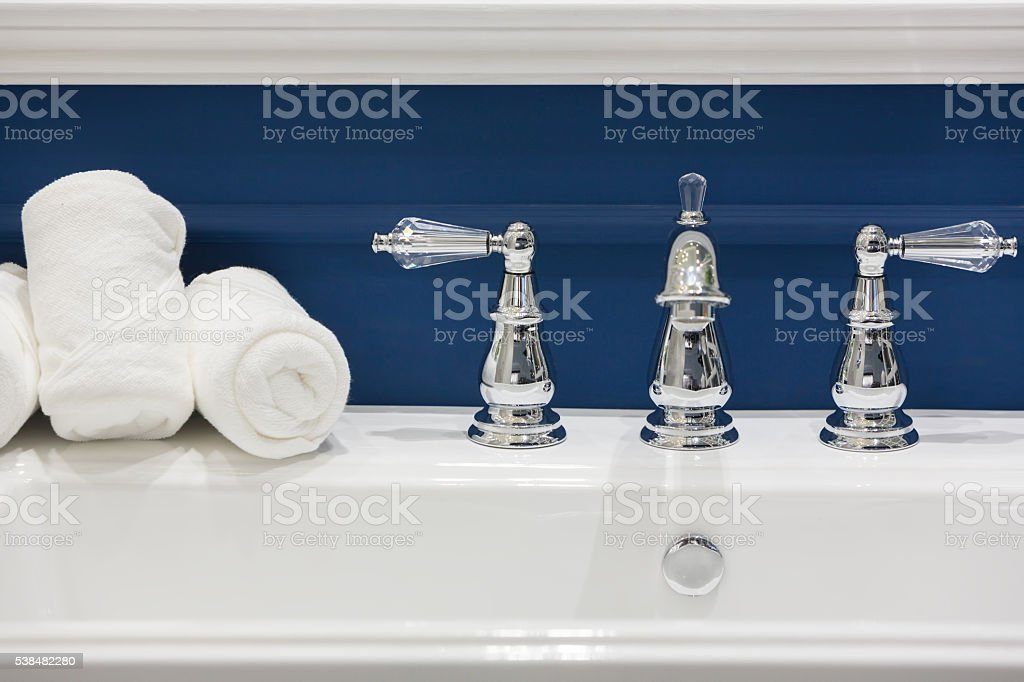 Three white hand towels on a white basin stock photo