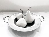 Original photo of three ceramic pears with stalks on a round engraved antique pewter dish with handles on a table has been transformed using the Enlight app to a smooth textured black and white elegant image