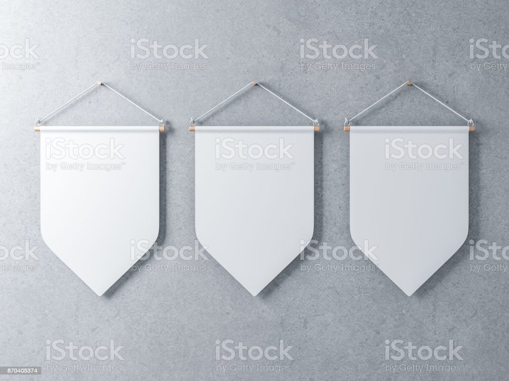 Three White pennants hanging on a concrete wall stock photo