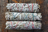 A close up image of three white sage smudge sticks used for spiritual clearing and healing.