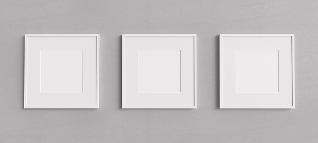 Three empty white picture frames with square shape on a grey wall. Blank Mockup for images and photos.