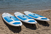 Three White Surfboards Resting on the Shoreline on the Beach.
