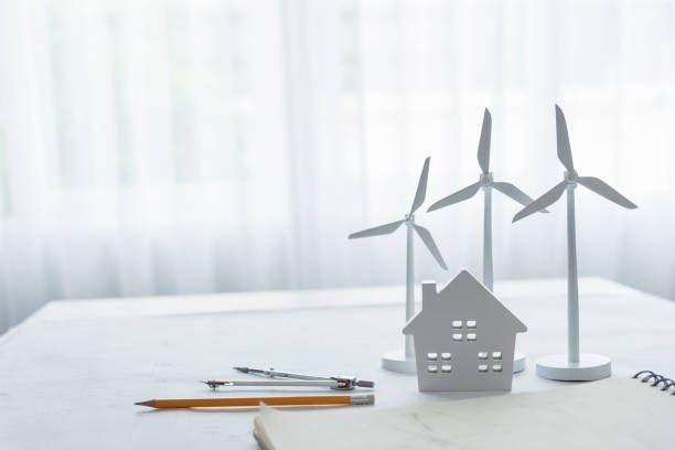 Three white wind turbine generating electricity on table in office modern stock photo