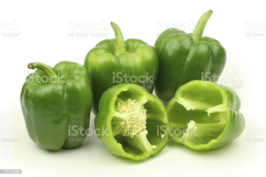 Three whole bell peppers and one pepper cut in half royalty-free stock photo