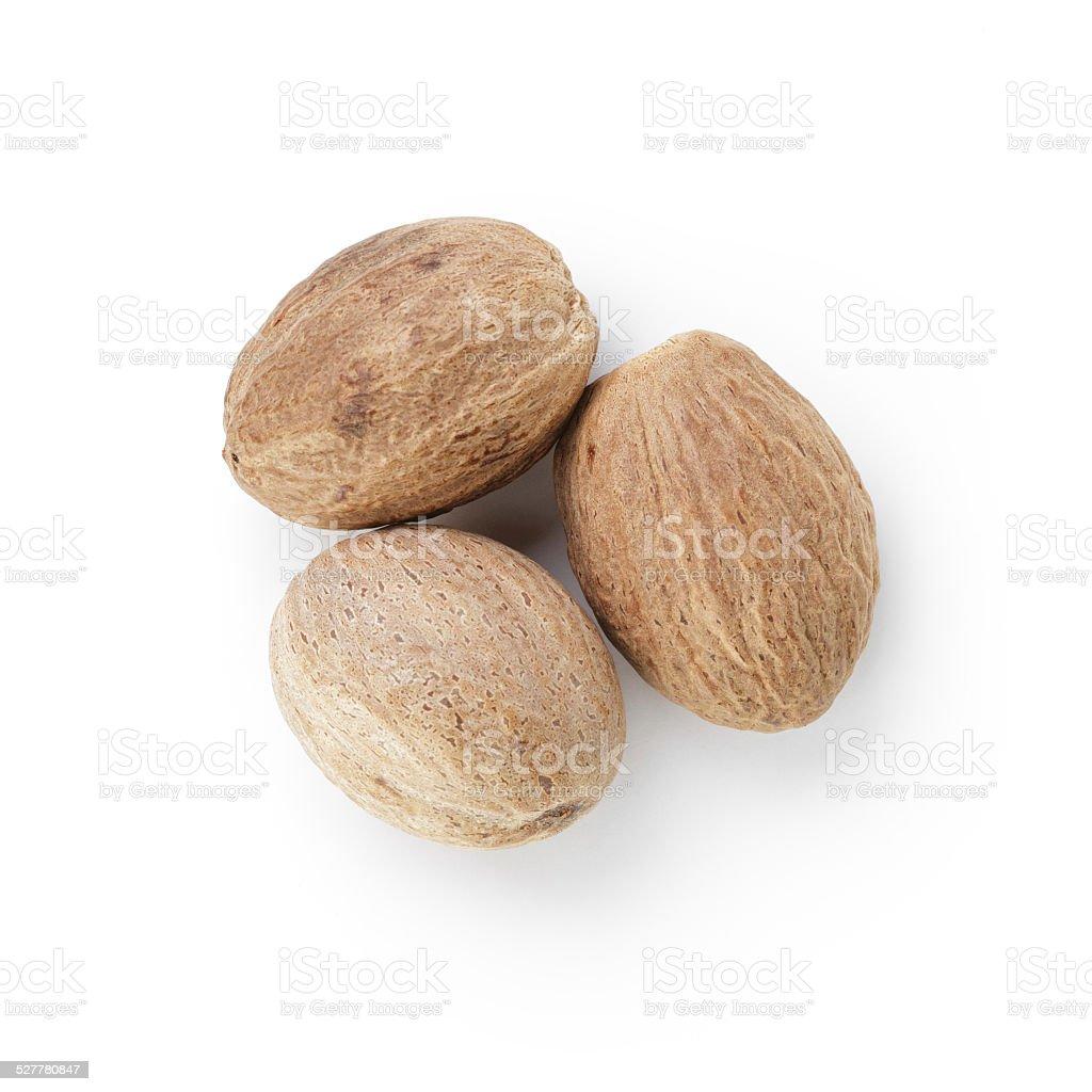 three whole dried nutmegs stock photo