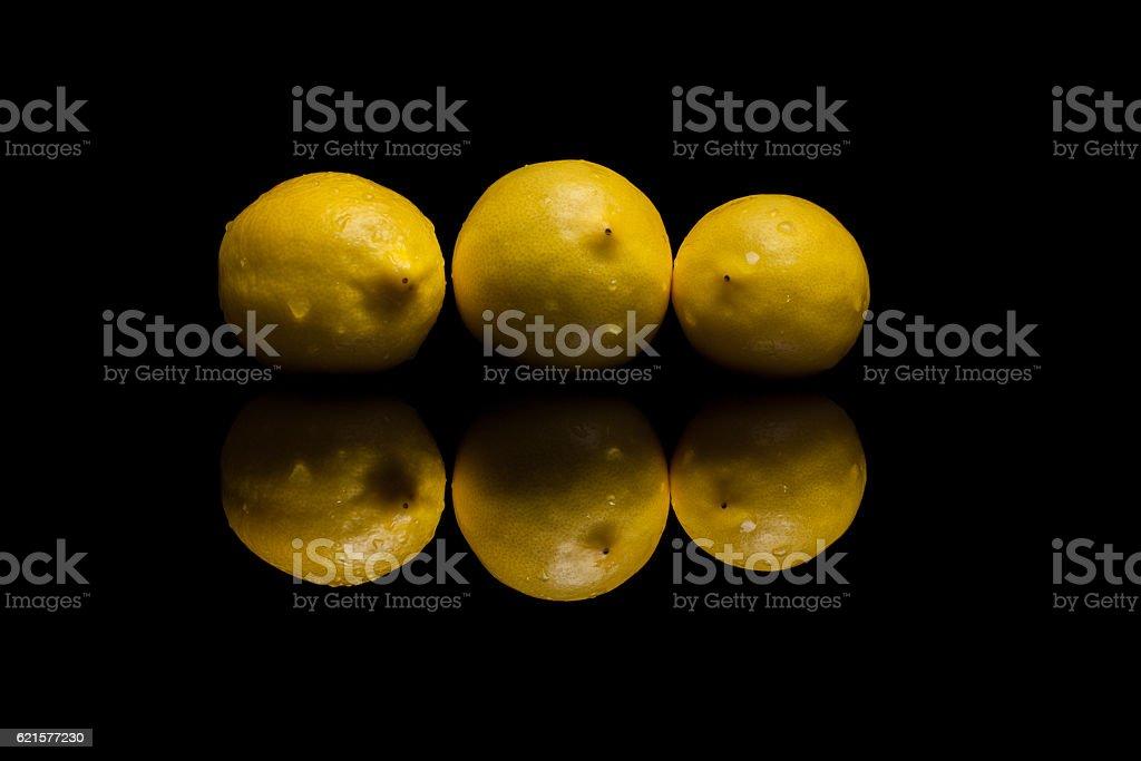 Three whole isolated yellow lemons on black background photo libre de droits