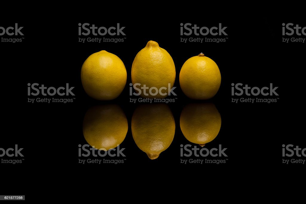 Three whole isolated yellow lemons on black background photo libre de droits