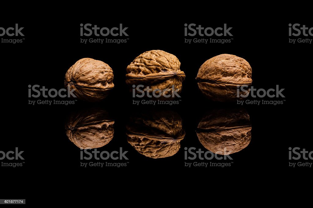 Three whole walnuts isolated on black background photo libre de droits