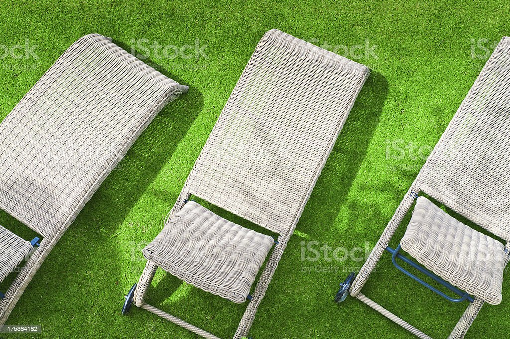 Three wicher lounge chairs on green lawn stock photo