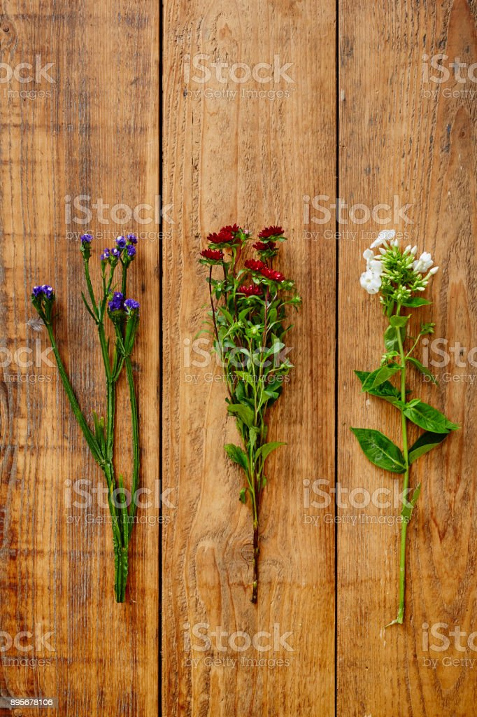 three wild flowers on wooden table graphic view stock photo