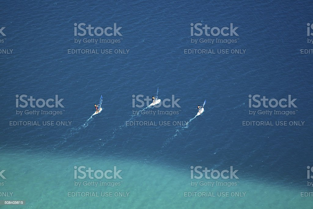 three wind surfers on action stock photo