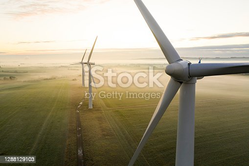 Aerial view of three wind turbines in the early morning fog at sunrise in the English countryside