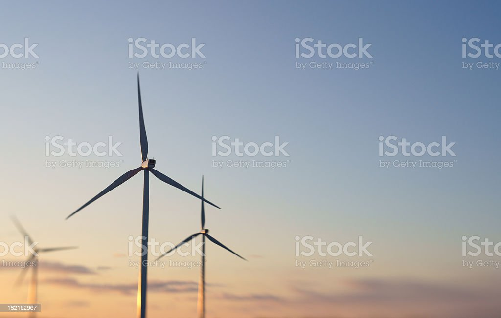 Three wind turbines at sunset. stock photo