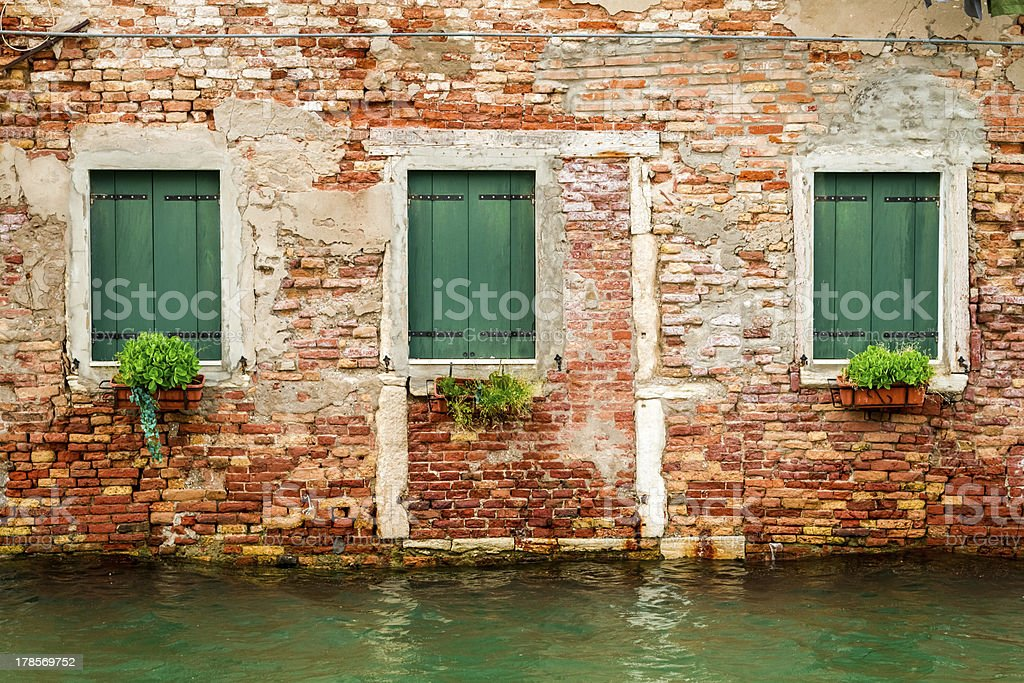 Three windows in ruined house on a canal, Venice royalty-free stock photo