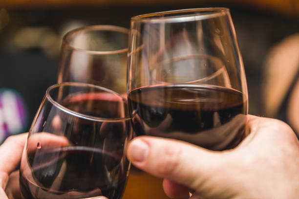 Three Wine Glasses Touching Three people touch their drinks together in a