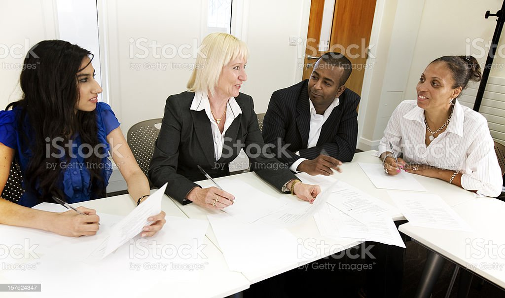 Three woman and a man attending and having a discussion at a business meeting royalty-free stock photo