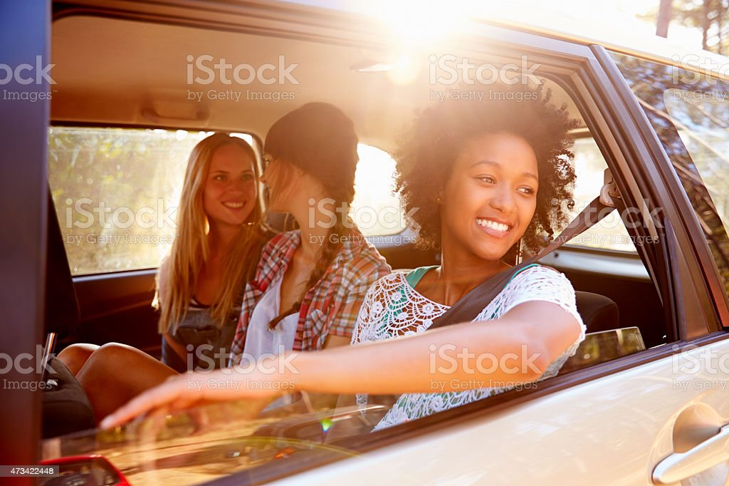 Three woman smiling in the backseat of a car stock photo