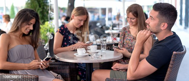 649172938istockphoto Three women addicted to their smartphones. They do not pay attention to their friend. 1098288914