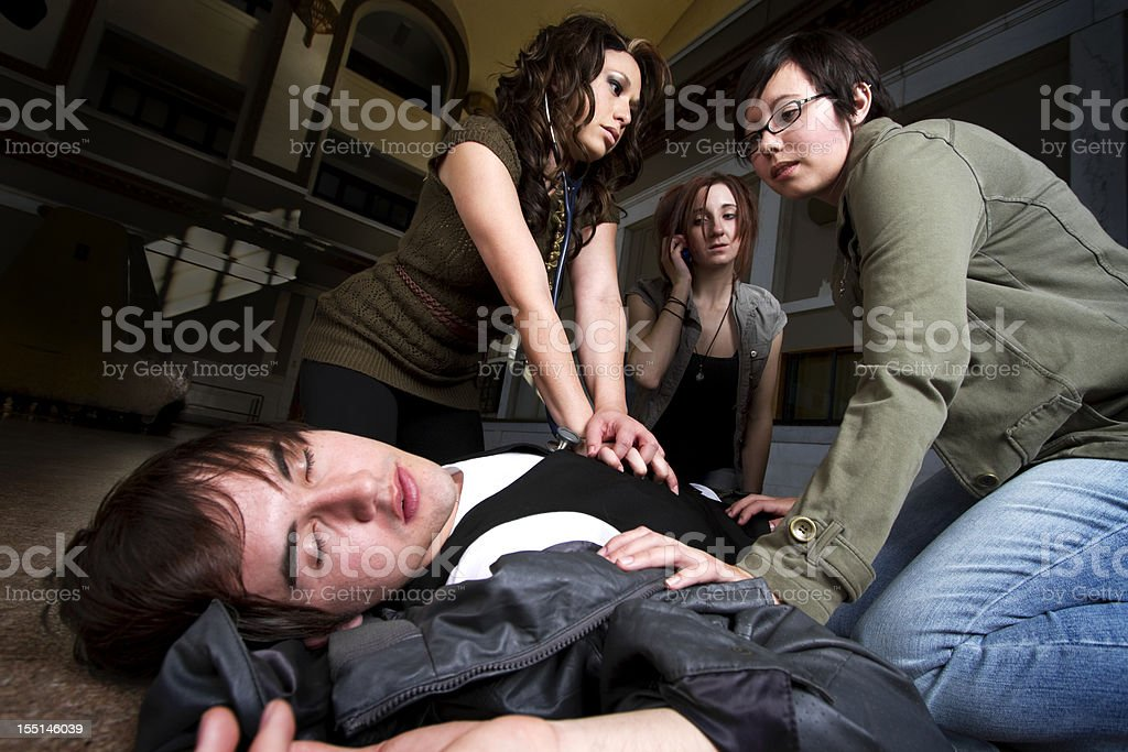 Three women administer CPR to a young man stock photo