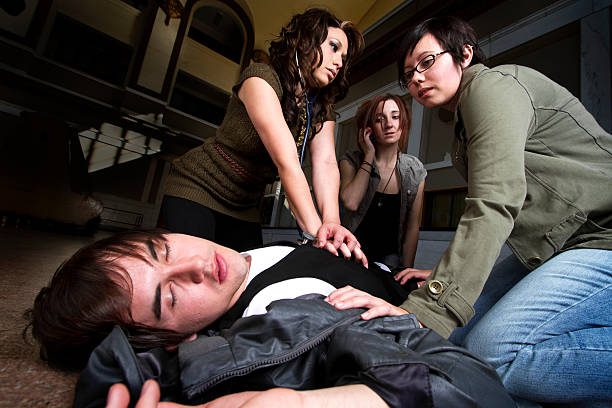 three women administer cpr to a young man - incidental people stock pictures, royalty-free photos & images