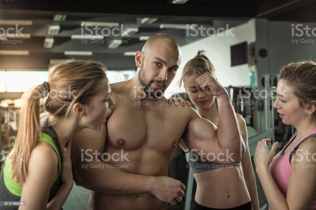 Three women admiring mens big muscles at gym stock photo