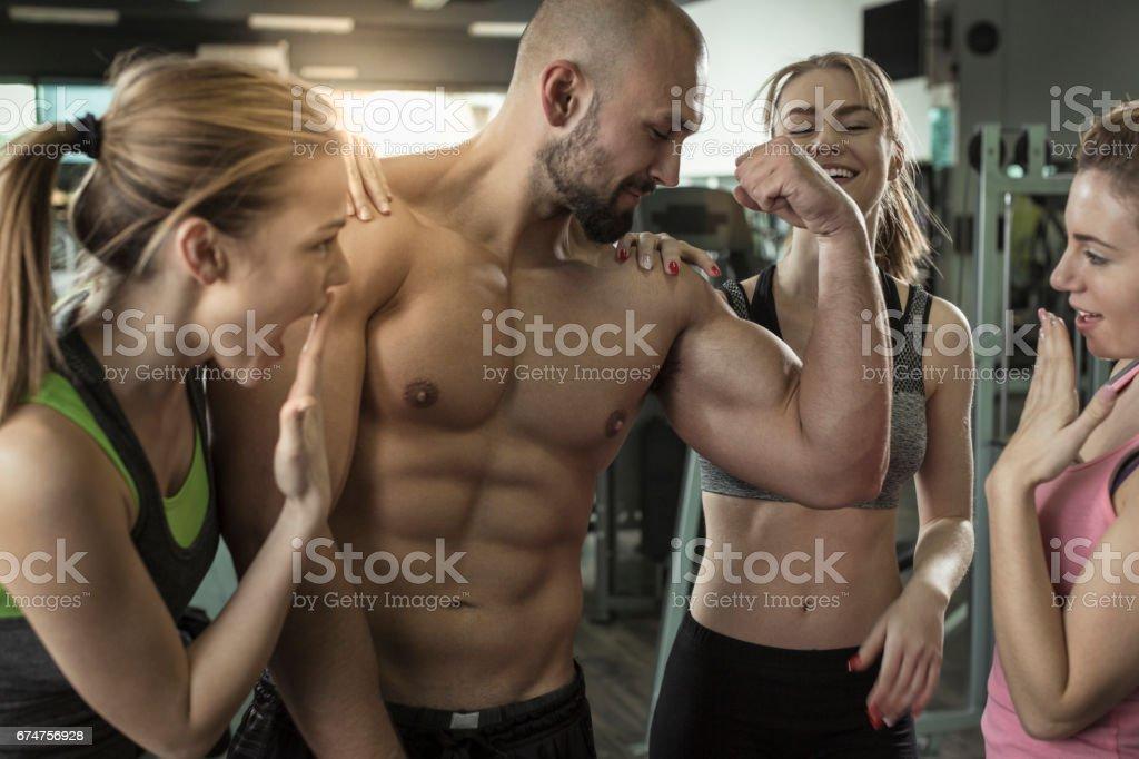 Tres mujeres admirando hombres grandes músculos en el gimnasio - foto de stock