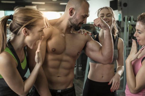 Three women admiring mens big muscles at gym stock photo