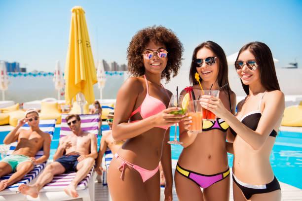 tres damas internacionales calientes mejores amigos tienen bebidas en la fiesta de piscina, novios son todo ellos y sonriente, mintiendo en sillas de playa, tomar el sol en club chill de verano superior de techo - solteros jóvenes fotografías e imágenes de stock
