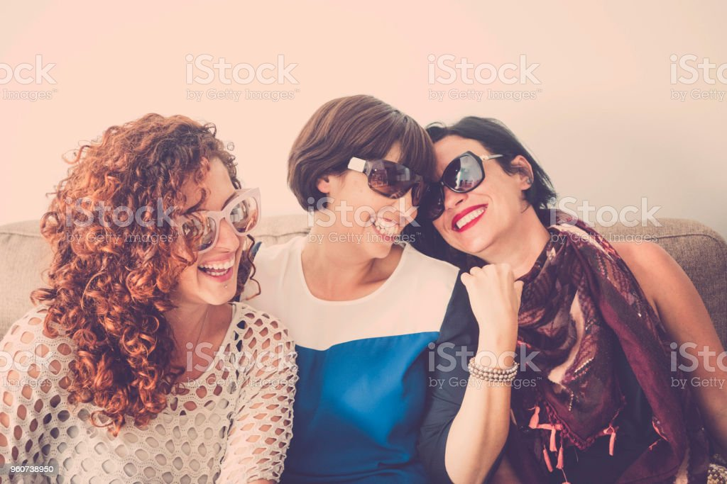 three women caucasian people group having fun at home with craziness and happiness together. stock photo