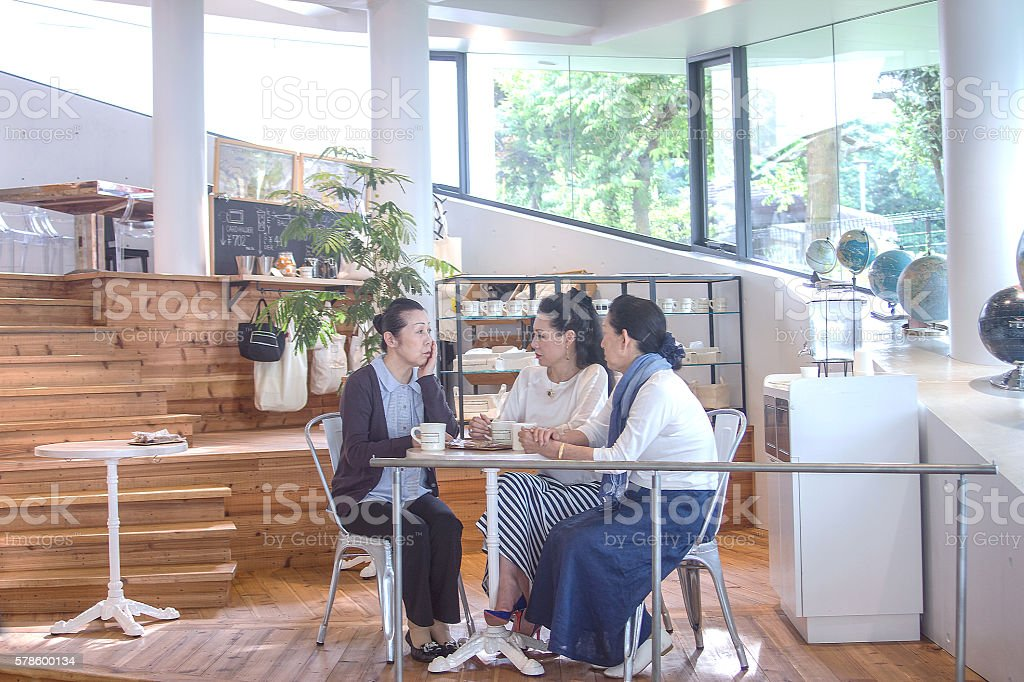 Three women chatting at a coffee shop stock photo
