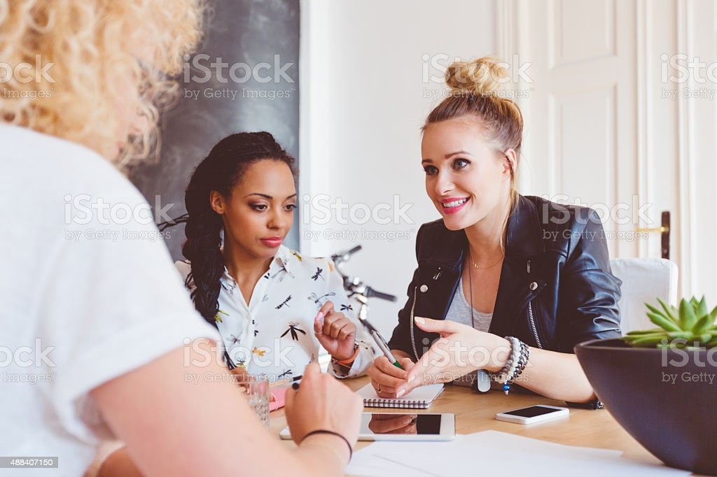 Three women discussing in an office stock photo