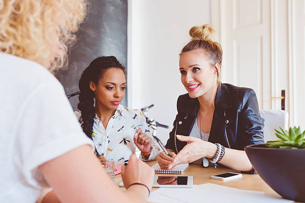 Three women discussing in an office Start-up or advertising agency. Three women - caucasian and afro american - sitting at the table in an office and discussing. Digital tablet and smart phone ont he table. persuasion stock pictures, royalty-free photos & images