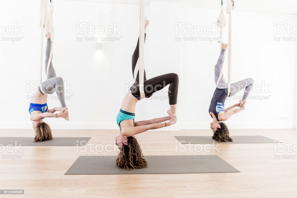 Three women doing aerial yoga exercises stock photo