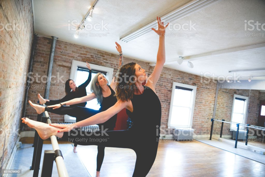 Three Women Doing Body Stretch on Barre stock photo