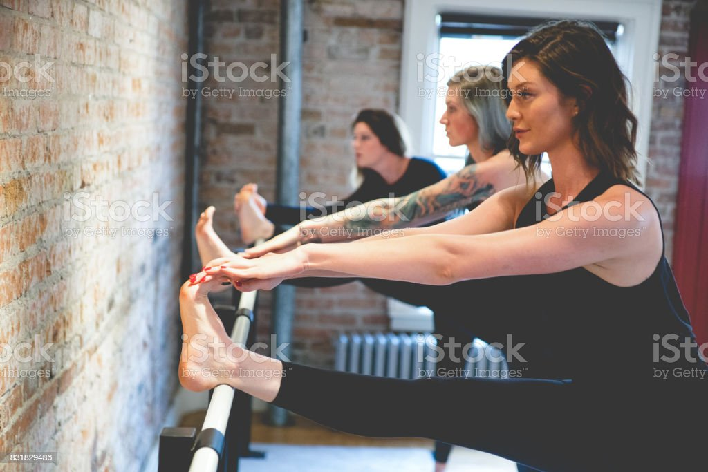 Three Women Doing Toe Stretches on a Barre stock photo