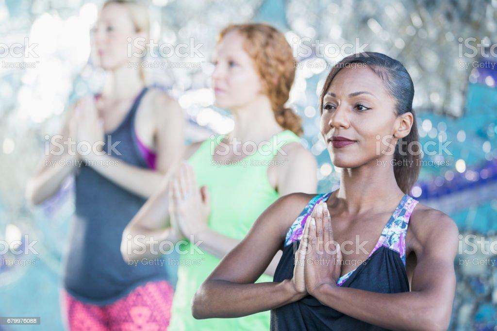 Three women doing yoga exercises stock photo
