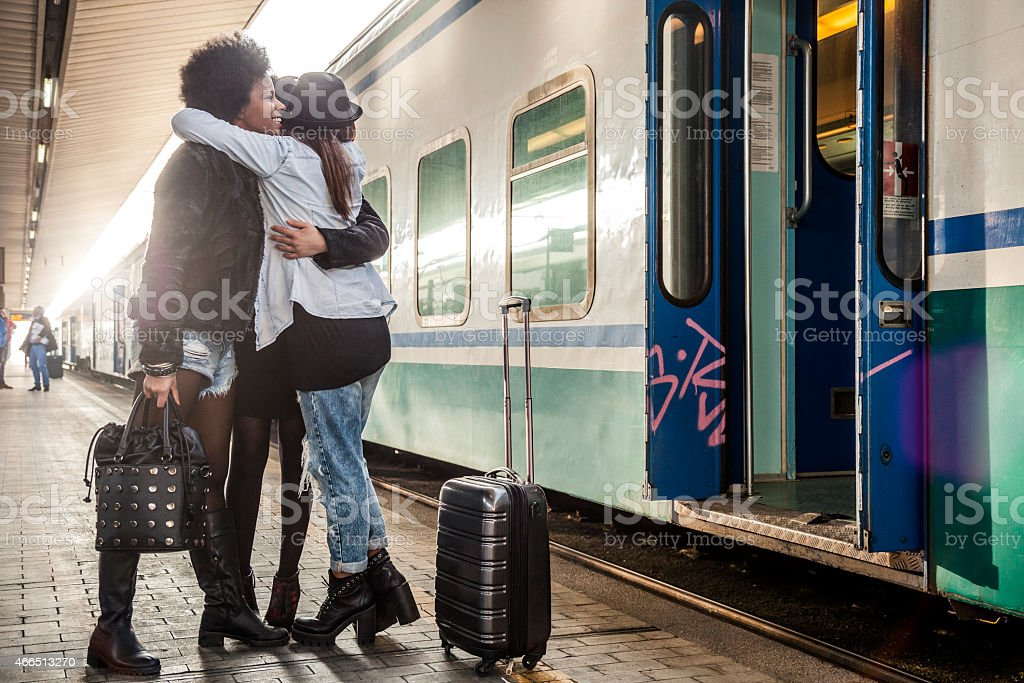 Three women friends greet at the train station stock photo