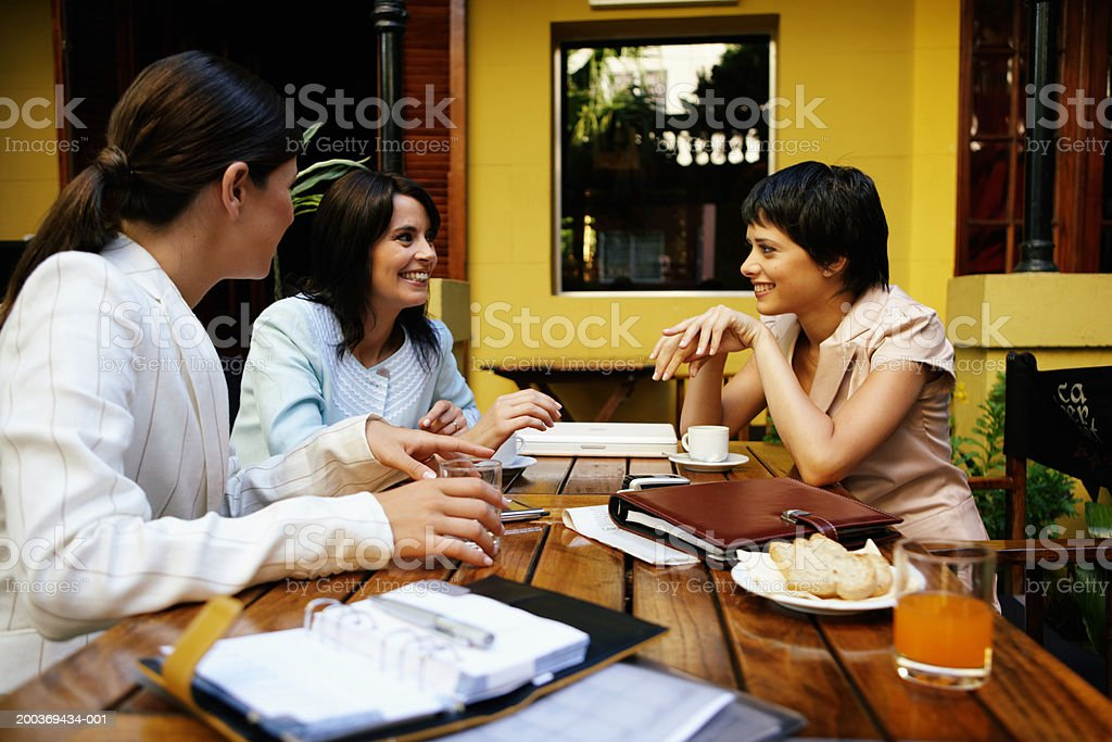 Three women having meeting in restaurant, smiling royalty-free stock photo