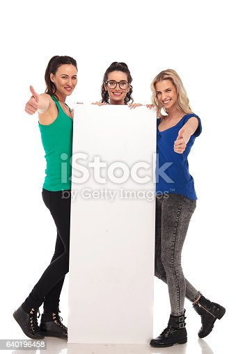 istock three  women holding a  billboard and make the ok sign 640196458