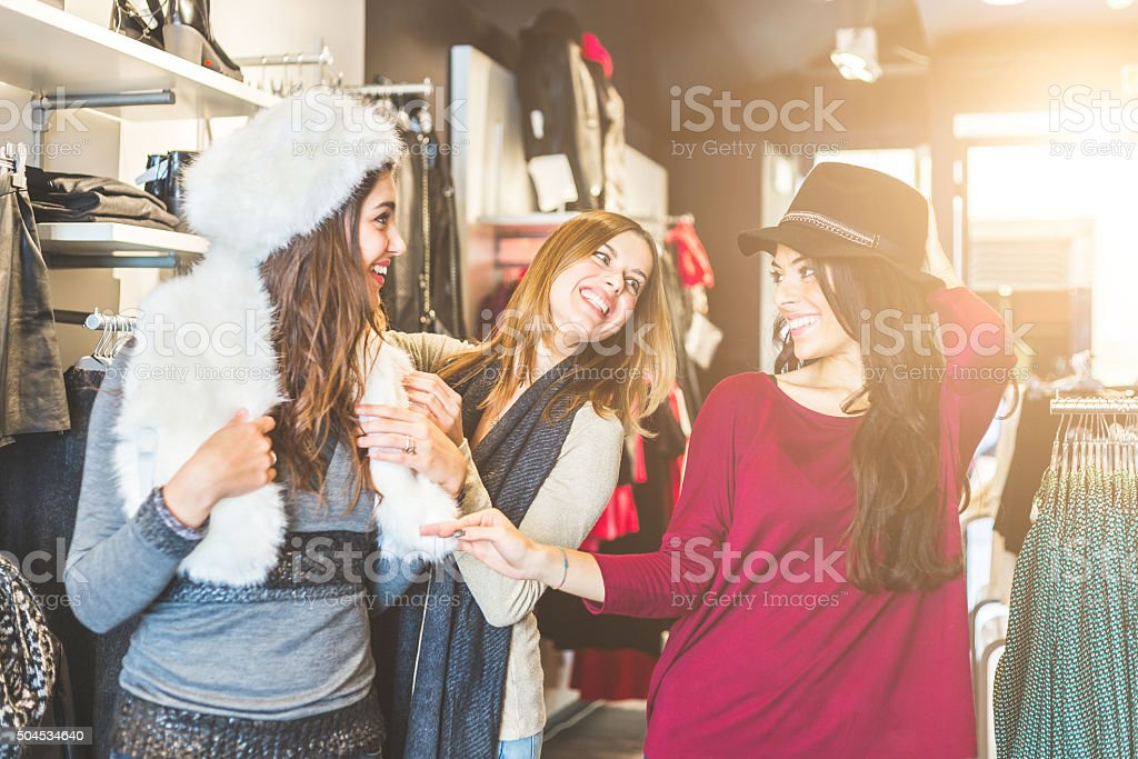 Three women in a clothing store enjoying shopping time stock photo