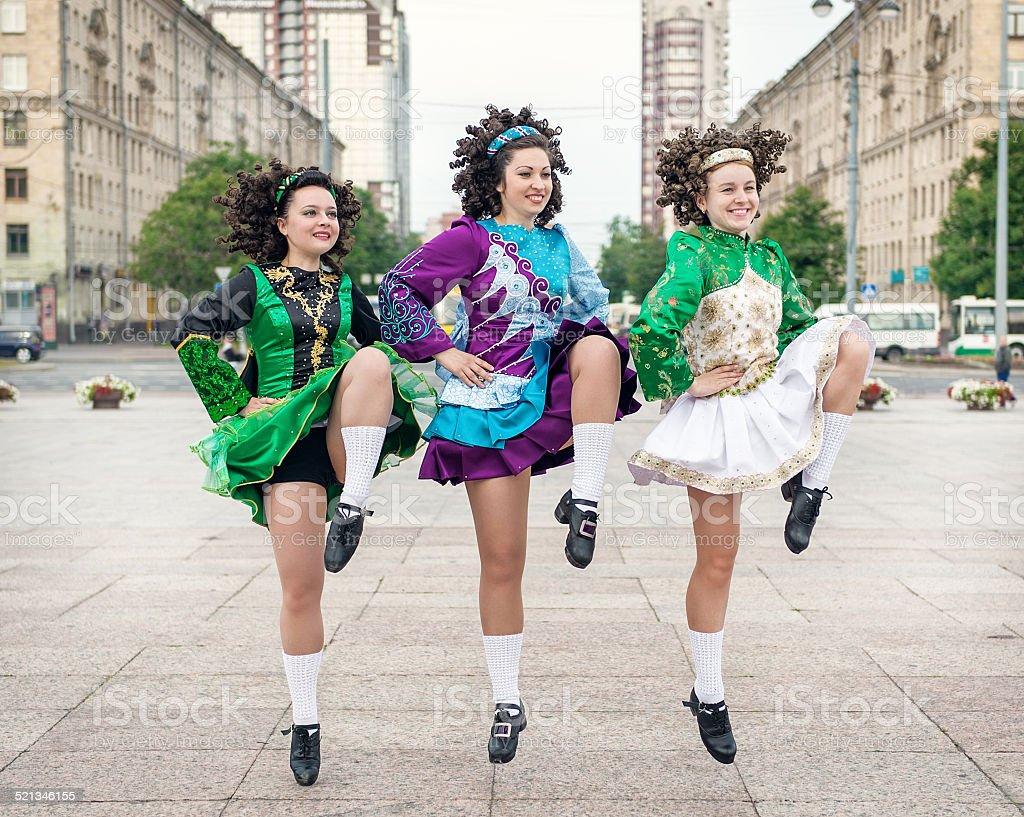 Three women in irish dance dresses dancing stock photo