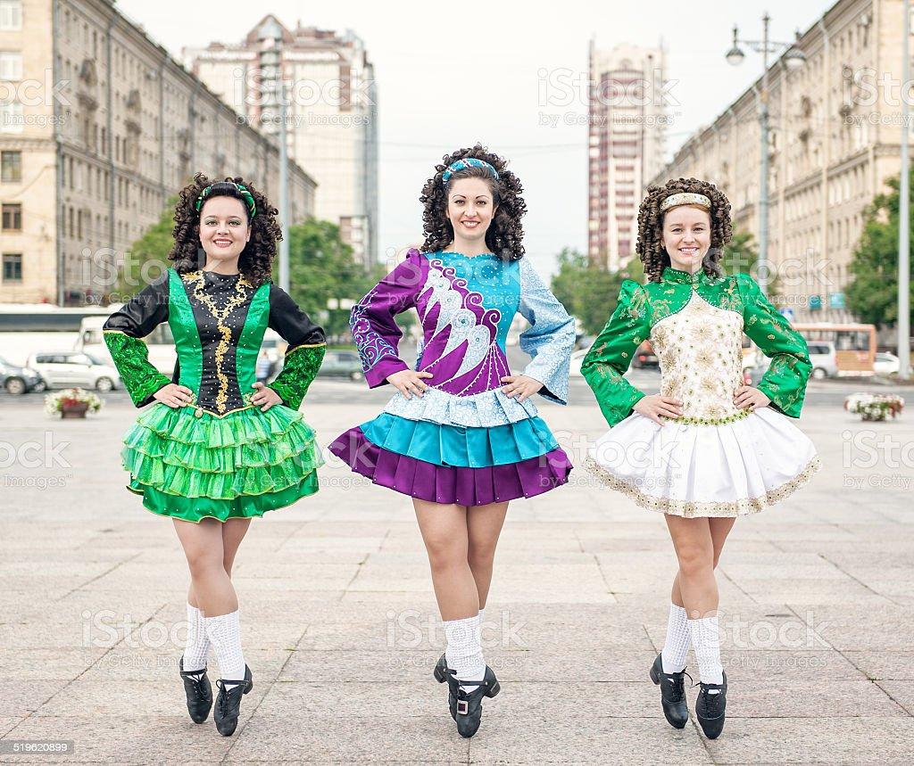 Three women in irish dance dresses posing stock photo