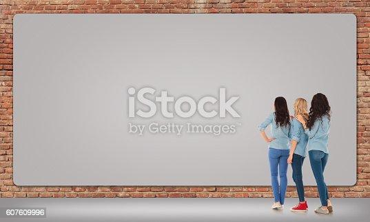 istock three women looking at a big blank billboard 607609996