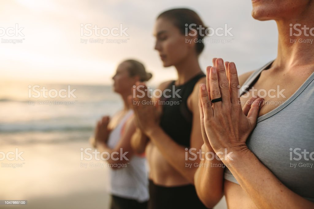 Three women meditating at the beach stock photo