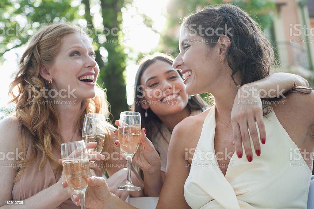 Trois femmes en plein air lors d'une fête avec champagne et souriant - Photo